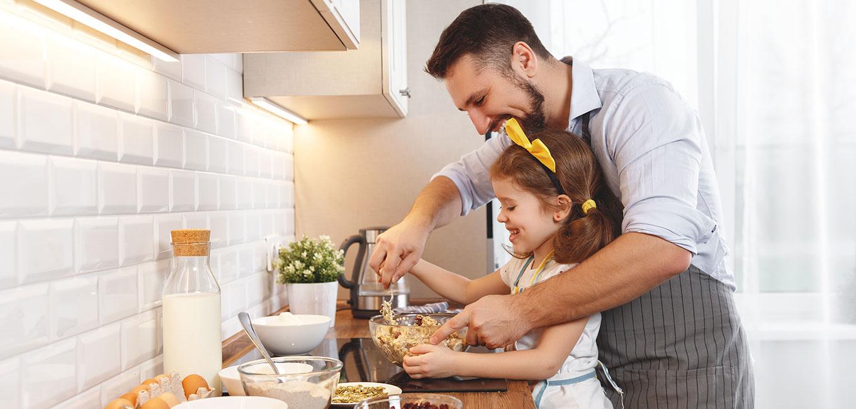 Padre con hija felices cocinando